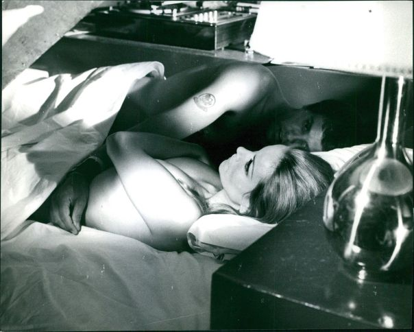 Claudine Auger lying down with Giuliano Gemma on bed