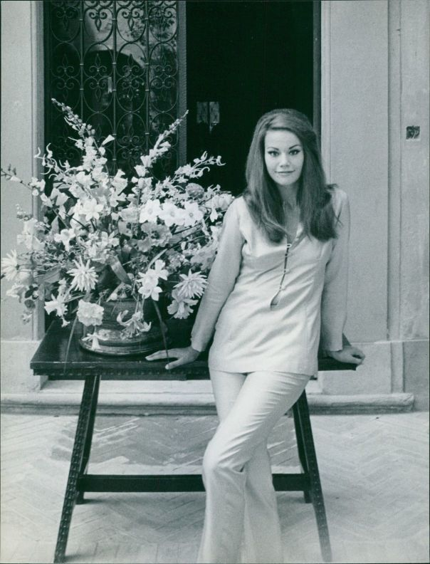 Claudine Auger posing beside a flower arrangement.- Jul 1966