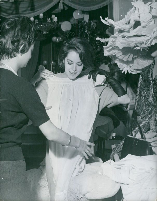Susan Kohner putting a dress over her clothes.