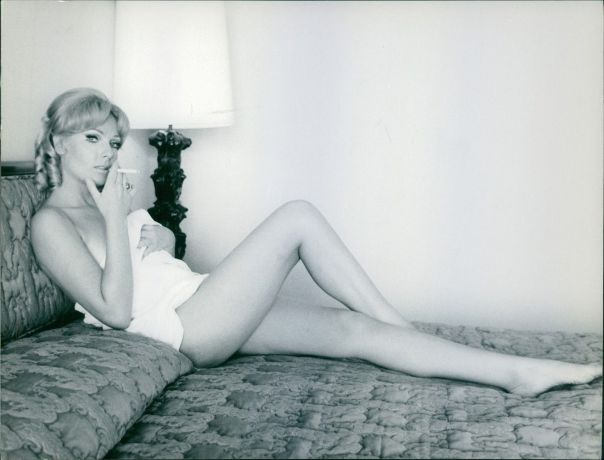 Thordis Brandt smoking cigarette on bed, covering her naked bo